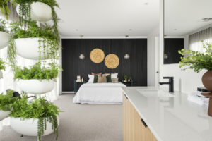 Residential Attitudes - Bedroom with large ferns and wooden bedboard