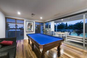 Residential Attitudes - Pool table with wooden floor and swimming pool in background
