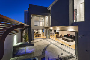 Residential Attitudes - Outside view of two story house with glass wall and open plan porch