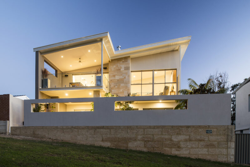 Residential Attitudes - Side view of two story house with lights on
