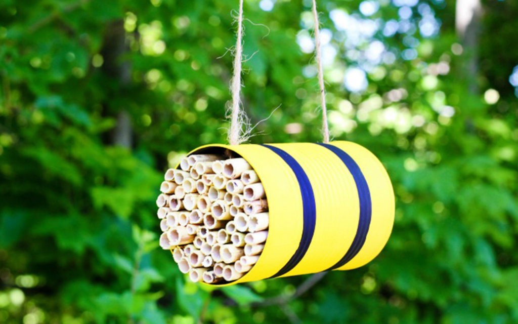 Suspended yellow bee hotel with bamboo materials.